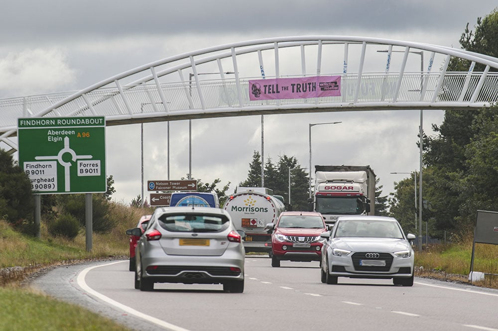 Thousands of vehicles pass under the bridge where XR Forres display their protest messages. Pic: Marc Hindley